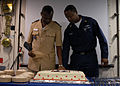 US Navy 090119-N-1688B-462 Lt. Jean Pierre Tine, Senegal Navy and Aviation Boatswain's Mate (Handling) 1st Class Leonard Starr cut a cake during a Martin Luther King Jr. remembrance ceremony aboard the amphibious transport dock.jpg