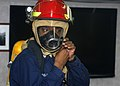 US Navy 110429-N-MM360-048 Ship's Serviceman 3rd Class Gregory Charles dons firefighting gear during a general quarters drill aboard the guided-mis.jpg
