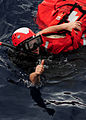 US Navy 111012-N-ED900-126 Search and rescue swimmer Fireman Walter May recovers Oscar, a man overboard rescue mannequin, and signals to be lifted.jpg