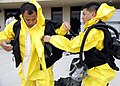 US Navy 111020-N-CW427-032 Hospitalman Garbriel Bacolod, right, assists Hospital Corpsman 3rd Class Rupert Ramirez don a hazardous material suit.jpg