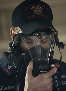 US Navy 120124-N-PB383-163 Damage Controlman 1st Class Justin Kuhlman demonstrates how to properly don a breathing apparatus.jpg