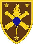 a brown shield shaped patch with a yellow border. Yellow stars are in each corner, surrounding crossed yellow cannons superimposed by a torch in yellow, which in turn is superimposed by a blue sea mine.