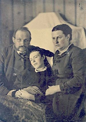 Victorian era post-mortem family portrait of parents with their deceased daughter.jpg