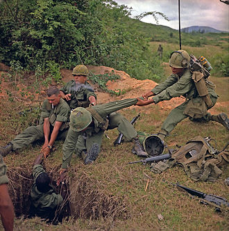 """Tunnel rat - Operation """"Oregon,"""" a search and destroy mission conducted by an infantry platoon of Troop B, 1st Reconnaissance Squadron, 9th Cavalry, 1st Cavalry Division (Airmobile), three kilometers west of Duc Pho, Quang Ngai Province. An infantryman is lowered into a tunnel by members of the reconnaissance platoon. Photograph taken 24 April 1967"""