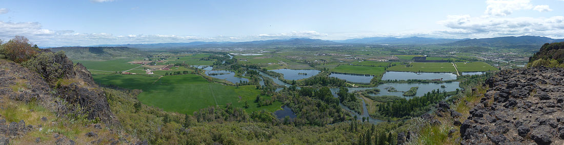 A river, seen from above, winds through flat farmland and a series of ponds on both sides of the stream. Buildings are scattered here and there across the landscape under a cloudy sky.
