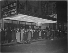 A crowd on the sidewalk in front of the lighted marquee of the Biltmore Theatre