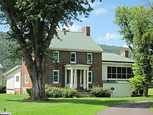 An image of two-story brick house with a green roof, a large front porch, and a tree in the foreground.