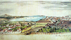 Watercolor depicting a scene overlooking a hillside on the slopes of which are many houses, and in the distance, ships at anchor in a wide river bordered by hills