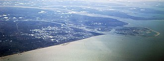 Westland (municipality), Netherlands - Aerial view of Westland (in the image center); behind it: Hook of Holland (the sharp-shaped promontory), Europoort (in between the two rivers), and Maasvlakte (protruding into the sea)