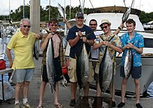 Photo of 6 men, four of whom are holding up tuna