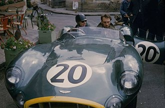 Tony Brooks (racing driver) - Tony Brooks parked outside the 1957 Le Mans Aston Martin base, the Hotel de France, at the wheel of his DBR1 race car.