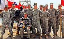 Thirteen US Army soldiers are posing for another camera (not seen) with a statuette of their beaver mascot and a red guidon. One soldier is sitting in front of the rest, wearing a harness and yellow diver's helmet. To the back-right of the group, a number of flags wave in the wind.