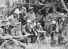 Australian and US soldiers planning operations amidst a jungle setting