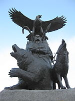 A life-sized bronze statue of an Indigenous person and eagle above him; there is a bear to his right and a wolf to his left, they are all looking upwards towards a blue and white sky