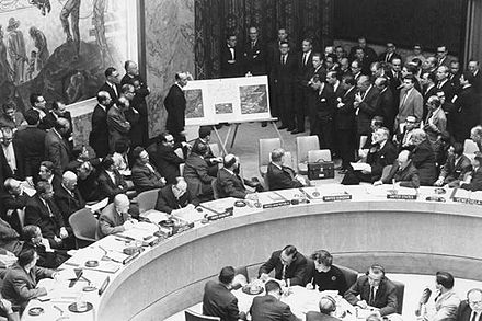 Adlai Stevenson shows aerial photos of Cuban missiles to the United Nations, October 25, 1962. Adlai Stevenson shows missiles to UN Security Council with David Parker standing.jpg