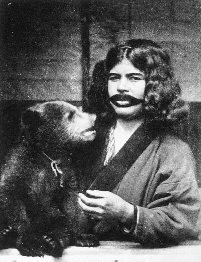 Ainu woman with mouth tattoos and live bear