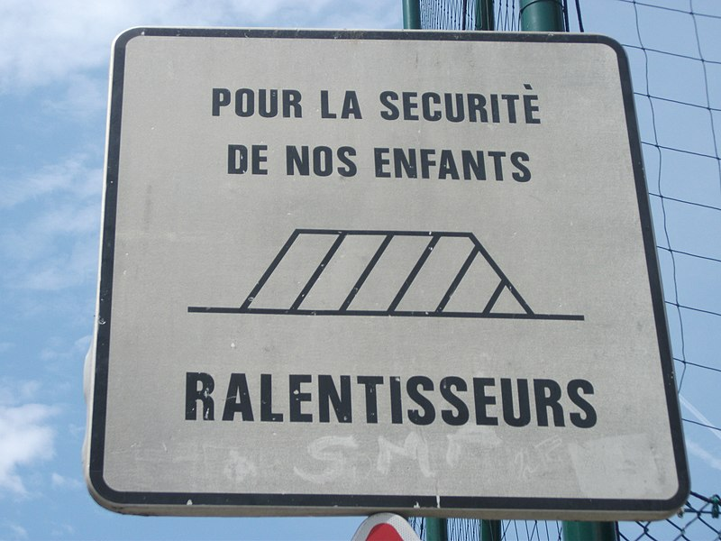 "Old non-regulatory sign announcing traffic calming on Alphonse Daudet Avenue, in Salon-de-Provence, Bouches-du-Rhône, Provence-Alpes-Côte d'Azur, France. Made in 1985. ""For childrens' security: traffic calmings"" (slow down)—2856"