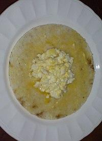 Arepa con margarina y quesito desmenuzado.