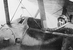 Close-up photograph of the side of an aeroplane. A man wearing a cap and with goggles on his forehead is seated in the cockpit.