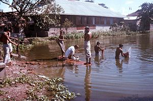 Bangladeshis bathing in Patuakhali Town
