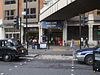 "Across a road with a London taxi and a car is an entrance. This has people standing in it and above is a blue rectangular sign reading ""BARBICAN STATION"" in white and above this is a bridge linking the building"