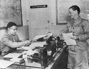 A woman in uniform hands papers to Smith, who is seated behind his desk and wearing glasses.