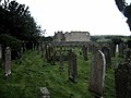 Bewcastle, the churchyard at St Cuthbert's, with the ruined castle beyond - geograph.org.uk - 958568.jpg