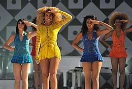 A woman in a yellow dress, flanked by three female dancers, salutes to the crowd