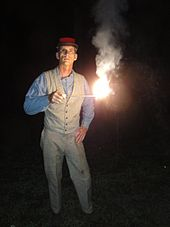 A man is standing in the dark. He is holding out a short stick at mid-chest level. The end of the stick is alight, burning very brightly, and emitting smoke.