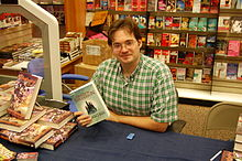 Photo of Brandon Sanderson at a book signing holding a copy of his book Elantris