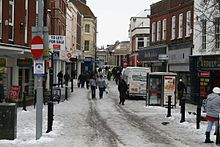 Street scene with pedestrians and vehicles in road lined with shops. There is snow on the ground.