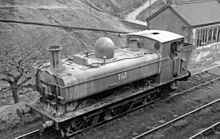 "A pannier tank locomotive, seen from above and to the front, is passing through hilly countryside. The locomotive, particularly at the front, is streaked with vertical stains. The lettering ""NCB 5774"" is shown on the side of the pannier tank."