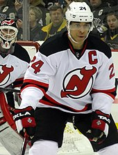 A defenseman in front of a goaltender during a game of hockey