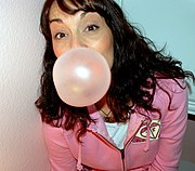 A woman blowing a bubble.