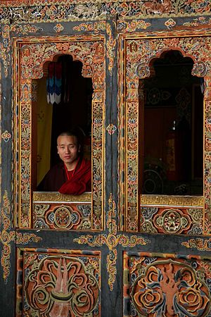 Buddhism in Bhutan - Bhutanese Buddhist monk looking out the window of a monastery.