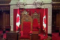The thrones for The Queen of Canada, and the Duke of Edinburgh (back) in the Canadian Senate, Ottawa are usually occupied by the Governor General and his/her spouse at the annual State Opening of Parliament. The chair in the foreground is for the speaker of the senate.