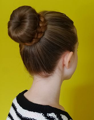 Bun (hairstyle) - A donut bun with the base of it is a half-finished donut bun; the loose hair that comes out of it (around the base of the bun) is being plaited into a half or full Dutch braid; the end of the braid is being wrapped around the bun and finally tucked under and hidden