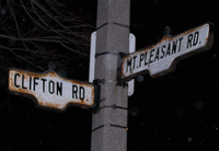 Two street signs on a cement pole at night