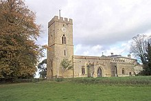 A stone church seen from the south, with a tower surmounted by a battlemented parapet on the left, and the nave with a porch and the chancel to the right