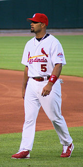Baseball batter in a red hat, white top and white pants, standing on baseball field for the Cardinals.