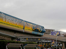 A monorail stamping a painted light cycle which leaves an orange trail behind. The second cart also has the Tron: Legacy title.