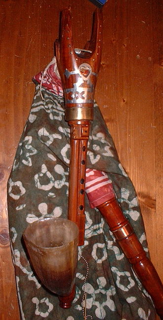 Duda - The chanter of a magyar duda. Note the double chanter and the carved animal head stock. The single finger hole of the kontra pipe is hidden behind the cow-horn chanter bell