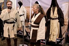 Photograph of a man and a woman dressed as Jedi in front of a display of costumes.