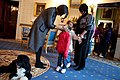 First Lady Michelle Obama greets a young visitor touring the White House during a surprise visit in the Blue Room with family dog Bo on the anniversary of the inauguration, Jan. 20, 2010.jpg