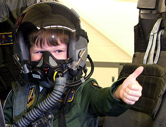 Military brat (U.S. subculture) - Young military brat gives thumbs up while wearing pilot's helmet at base special event.