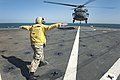 Flickr - Official U.S. Navy Imagery - A Sailor signals a helicopter to land..jpg