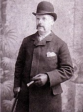 Man with a moustache wearing a bowler hat, topcoat, and leather gloves. He holds a cane in the left hand, and a cigar in the right.
