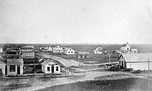 Black-and-white photo: ca. 20 one-story buildings on treeless prairie