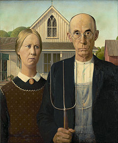 Man and woman with stern expession stand side-by-side. The man holds a pitch fork and wears glasses.