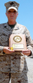 Gunnery Sergeant Camilla Lawson holding her GEICO Military Service Award, in Guantanamo.png